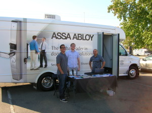 From left to right, Tony Jr., Sam, and Tony Sr. of Professional Lock & safe in front of ASSA ABLOY Mobile Showroom Truck